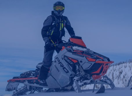 Person riding a red and white Polaris snowmobile